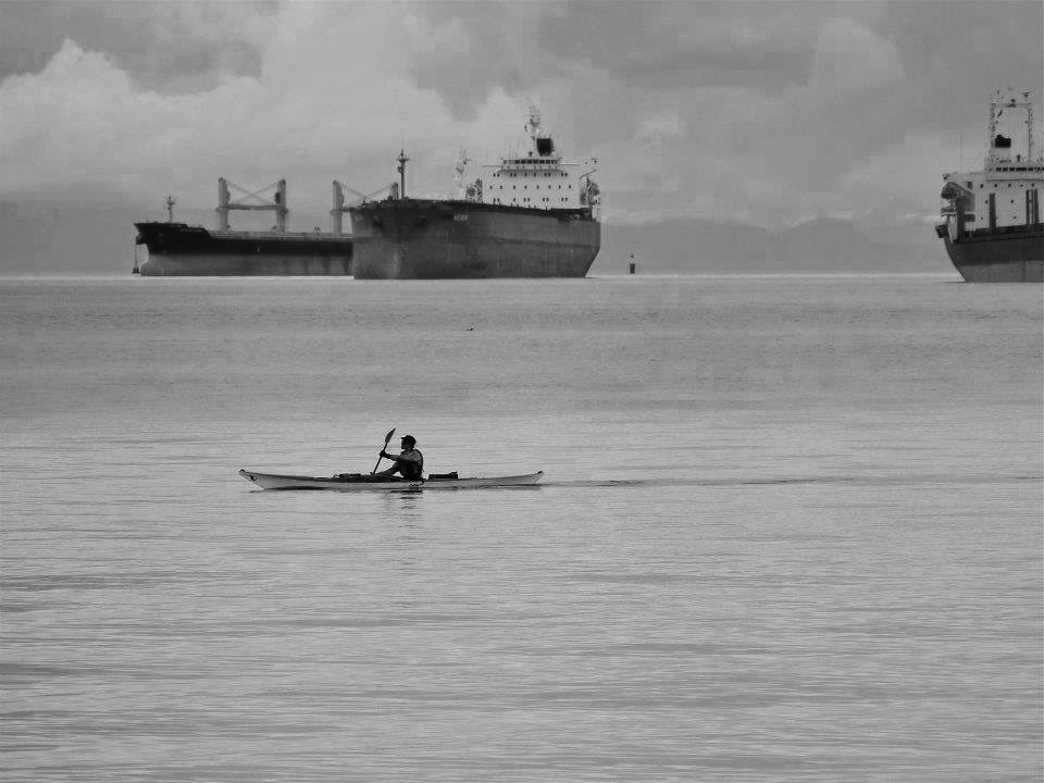Kayaker paddling off Stanley Park in front of cargo ships waiting to enter Vancouver harbour, BC.